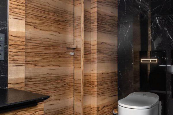 Połączenie drewnopodobnej faktury z czernią glazury zaprojektowane wnętrze Białystok